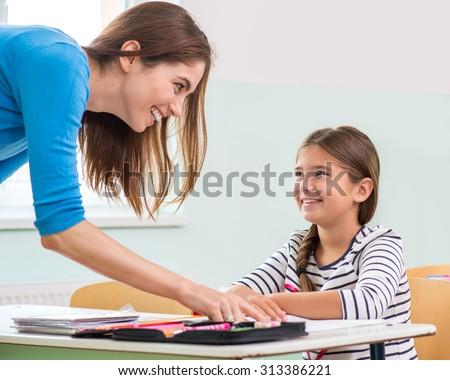 Female teacher shows the children the book, reading - stock photo