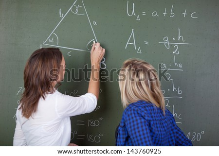 Female teacher solving a mathematics question on the blackboard while a female student standing behind and looking.