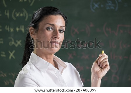 Female teacher standing in front of a chalkboard in a classroom - stock photo