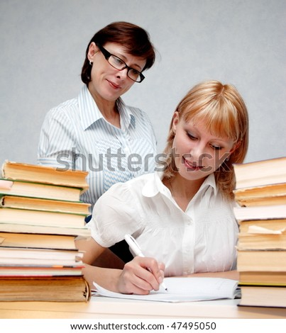 Female teacher supervises the student. - stock photo