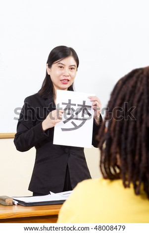 female teacher teaching chinese to african student - stock photo