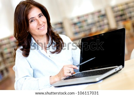 Female teacher with a laptop at the library - stock photo