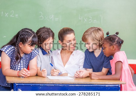 Female teacher with her multi ethnic classroom learning math. - stock photo
