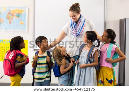 Female teacher with smiling children in classroom