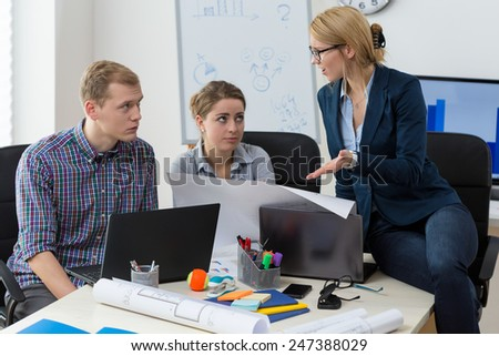 Female team leader being angry on her co-workers - stock photo