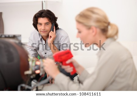 female technician working while the client is talking on the phone - stock photo