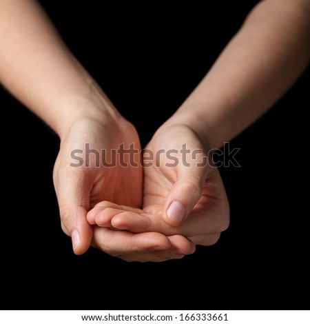 female teen hands begging for something, isolated on black - stock photo
