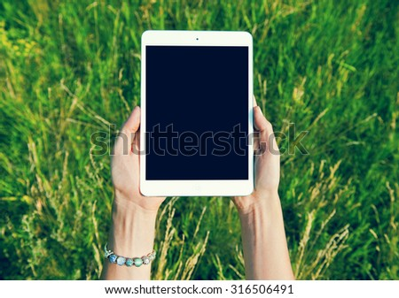 Female teen hands using tablet pc with black screen - stock photo