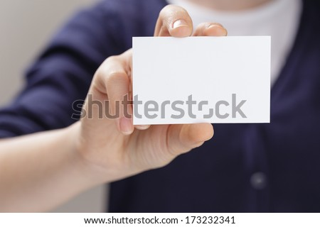female teen holding empty business card in front of camera, blurred background - stock photo