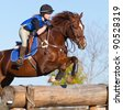 Female teen on cross country course jumps a horse over an obstacle - stock photo