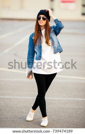 Female teen sits on asphalt road in urban wear and hat