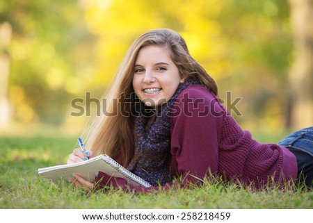 Female teen with braces taking notes while laying on ground - stock photo
