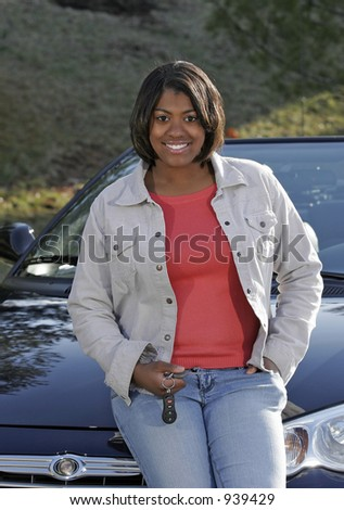 female teen with keys leaning on car - stock photo