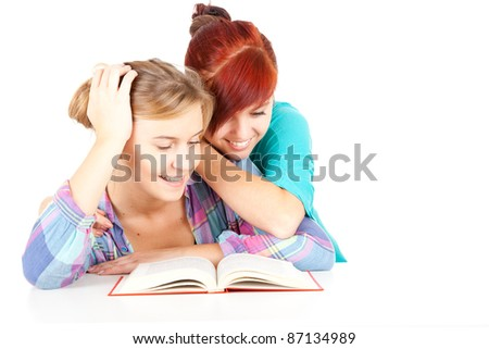 female teenage friends reading red book, white background - stock photo