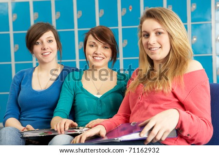 Female Teenage Students Relaxing By Lockers In School