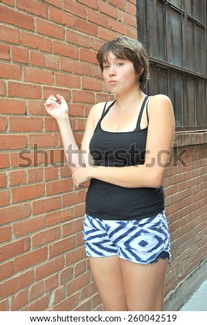 Female teenager expressions against a wall outside. - stock photo