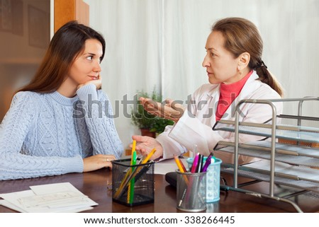 Female teenager patient listening the doctor about medicine at table - stock photo