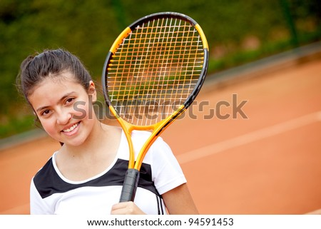 Female teenager playing tennis, holding a racket and smiling - stock photo