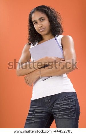 Female teenager posing holding a laptop - stock photo