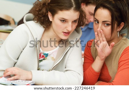 Female teenager whispering with another one in classroom - stock photo