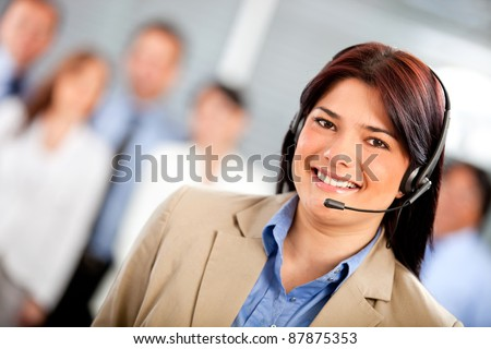 Female telemarketing agent smiling at a call center - stock photo
