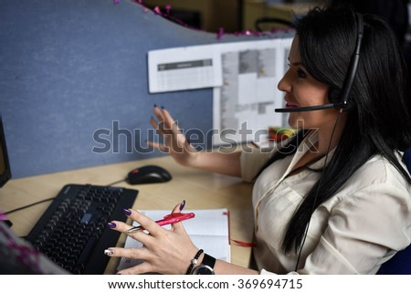 Female telesales agent in conversation with customers in call center, talking on the headset - explain details and gestures with hands - stock photo