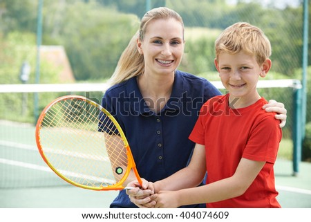 Female Tennis Coach Giving Lesson To Boy - stock photo