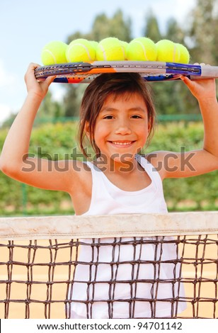 Female tennis player a racket and balls on top of her head - stock photo