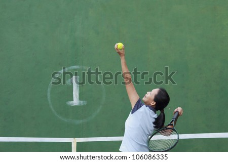 Female tennis player getting ready to serve - stock photo
