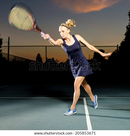 Female tennis player hitting the ball - stock photo
