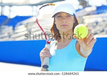 Female tennis player holding out tennis ball. Horizontal Shot.