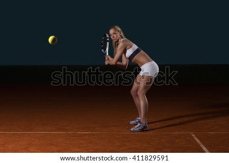 Female Tennis Player Reaching To Hit The Tennis Ball On Court - stock photo