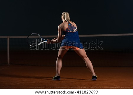 Female Tennis Player Reaching To Hit The Tennis Ball On Court - Back View - stock photo