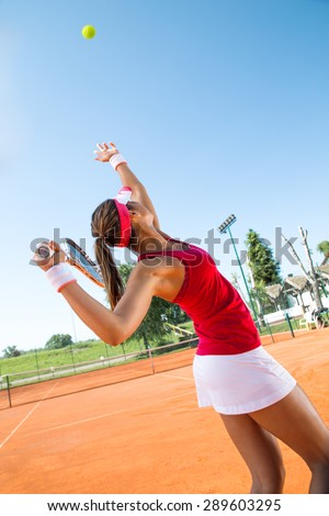 Female tennis player serving a tennis ball - stock photo