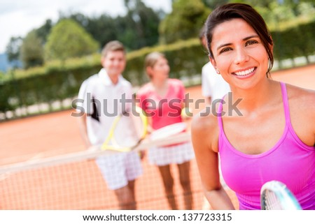 Female tennis player with a group of friends at the court - stock photo