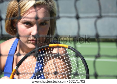 Female tennis player with determined stare through the net