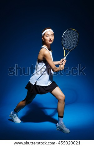 Female Tennis Player With Racket Ready To Hit A Tennis Ball - Isolated On Blue - stock photo