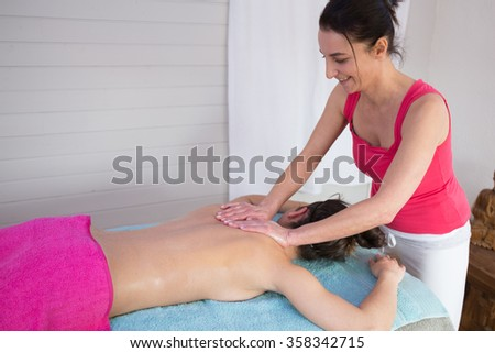 Female therapist hands doing a back massage on woman.