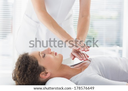 Female therapist performing Reiki over woman at health spa - stock photo
