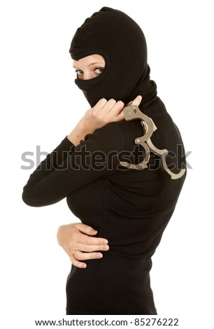 female thief in black balaclava and clothes with handcuffs - stock photo