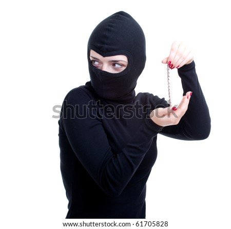 female thief in black clothes and balaclava keeping bracelet - stock photo