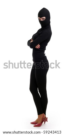 female thief in black clothes and balaclava  with crossed arms - stock photo