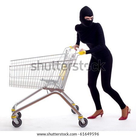 female thief in black clothes and balaclava with shopping cart - stock photo