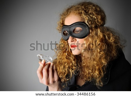 female thief stealing a diamond - stock photo