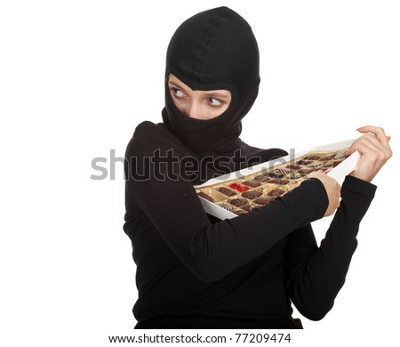 female thief with in black balacalava box of chocolates - stock photo
