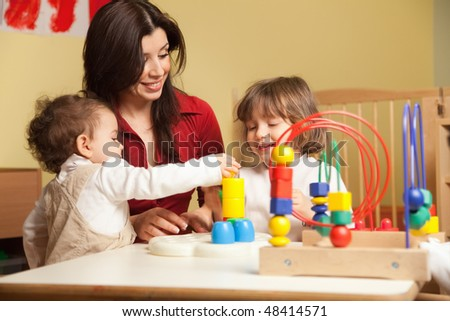 female toddler and 2-3 years girl playing with blocks toy in kindergarten. Horizontal shape - stock photo
