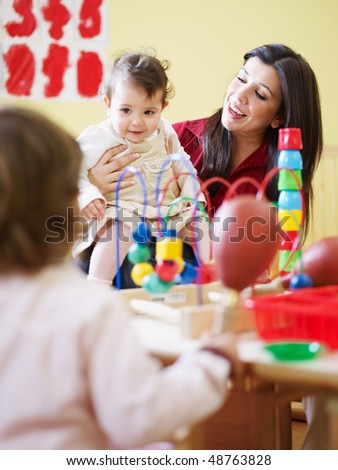 female toddler and 2-3 years girl playing with maraca in kindergarten. Vertical shape - stock photo