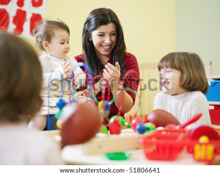 female toddler and 2-3 years girls playing with toys in kindergarten. Horizontal shape - stock photo