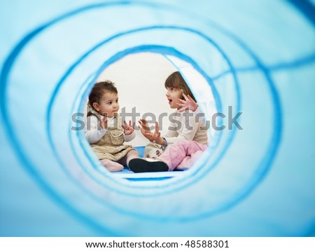 female toddler and 2-3 years old girls viewed from blue toy tunnel, clapping hands and singing. Horizontal shape, Copy space - stock photo