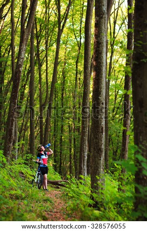 Female tourist and bicycle enjoying wood view